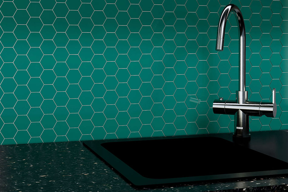Description: A faucet on a green wallDescription automatically generated with low confidence